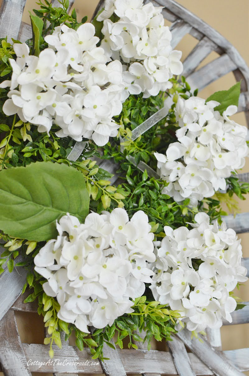 white hydrangea farmhouse wreath in a tobacco basket