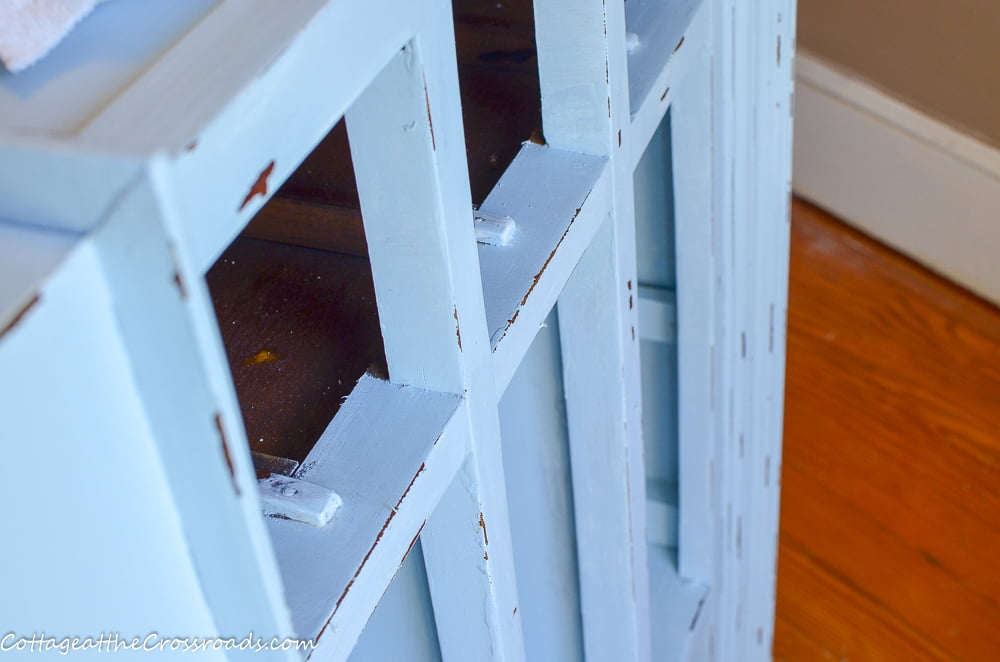 distressing a repurposed vanity painted with DIY chalk paint