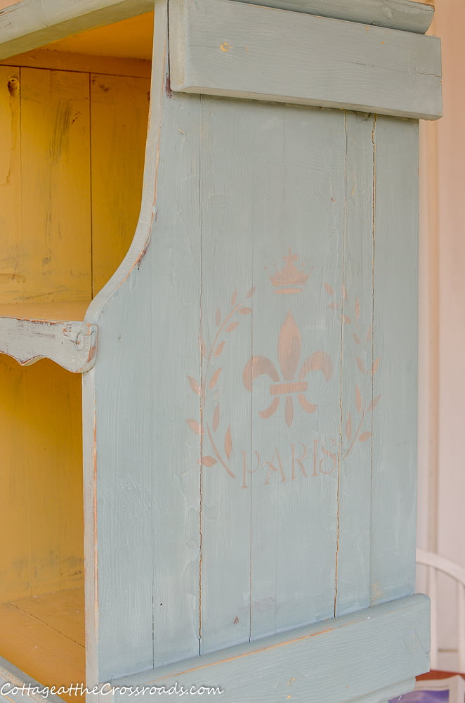 fleur-de-lis stencil on the side of a magazine rack