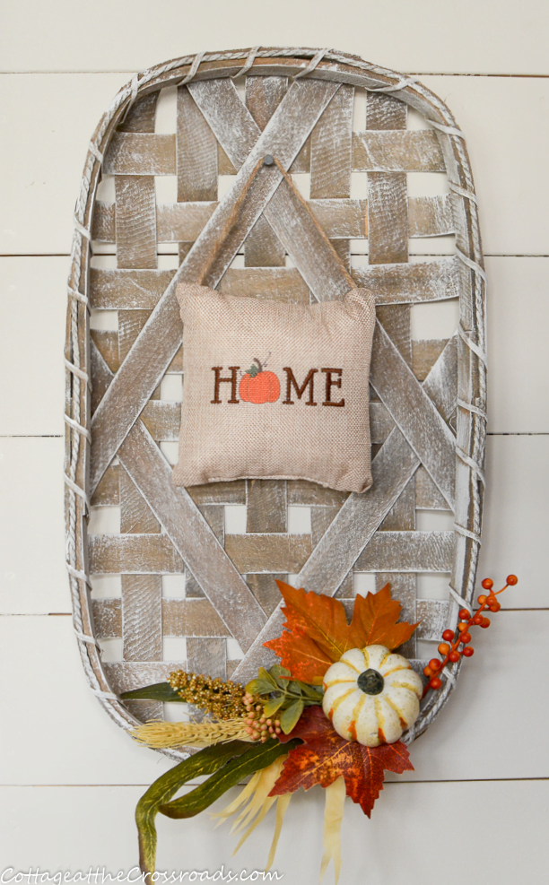 fall decorated tobacco basket in a mudroom