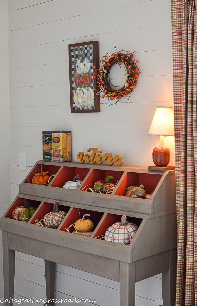 pumpkin lamp on a cubby filled with pumpkins