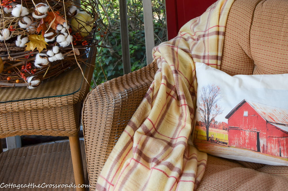 red barn pillow on a fall porch
