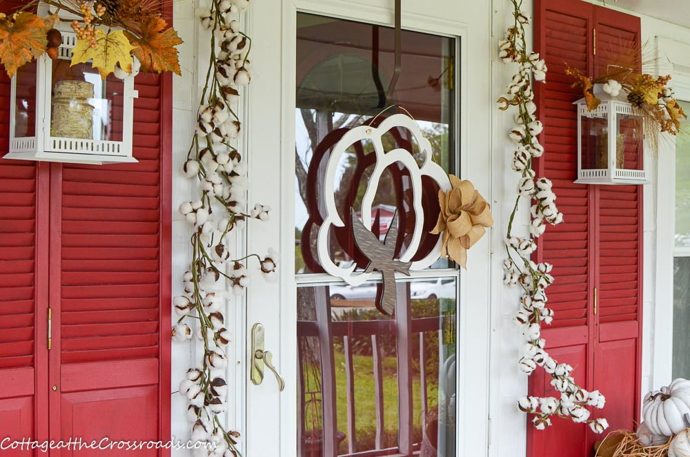 wooden cotton doorhanger on a cotton themed fall front porch