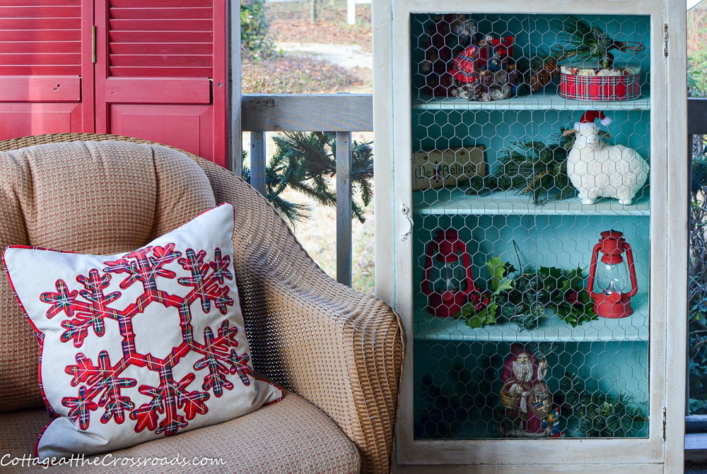 aqua jelly cupboard and a wicker chair on a Christmas front porch