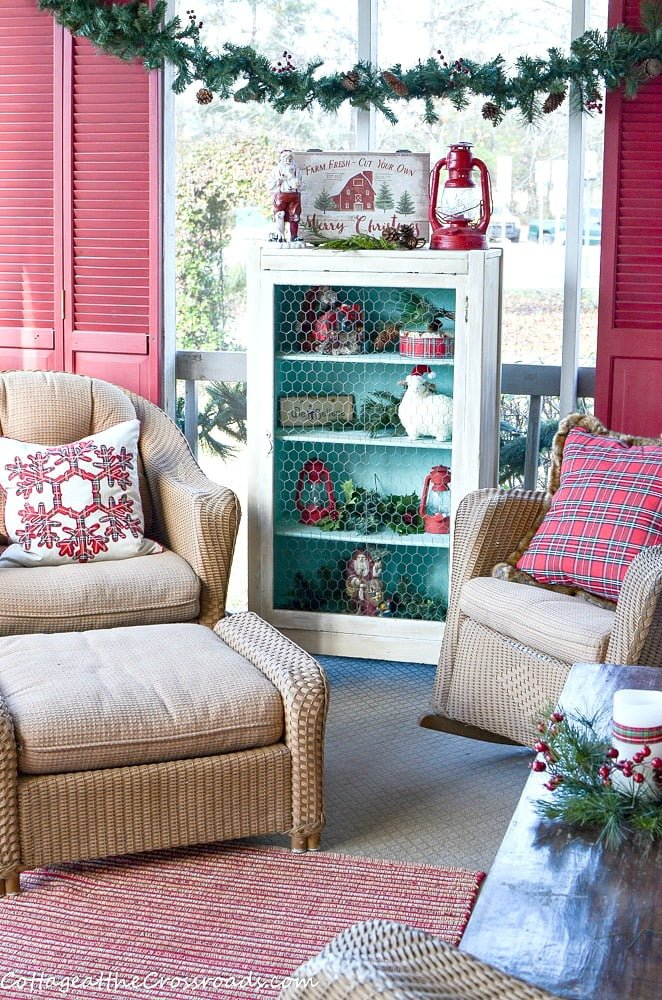 country cottage Christmas front porch decorated with red, aqua, and plaid
