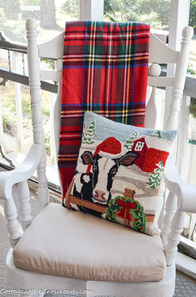 plaid throw and pillow in a rocking chair on a Christmas porch