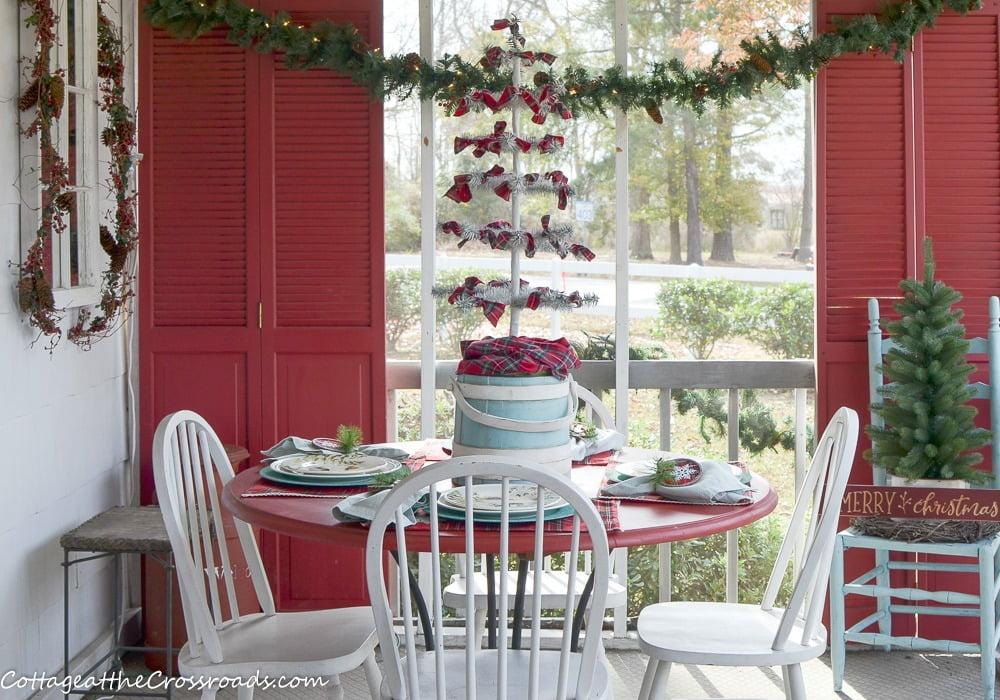 table on a plaid and aqua Christmas porch