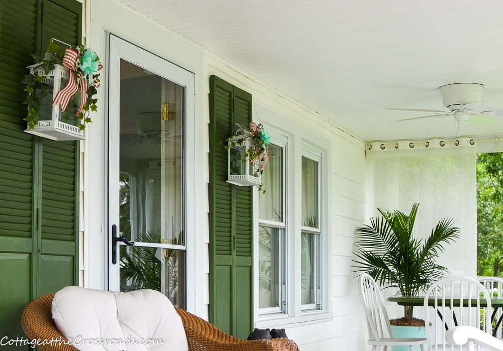 green repurposed closet doors used as shutters on porch