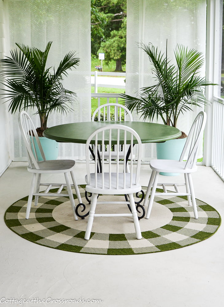 table, chairs, and palm trees on the porch