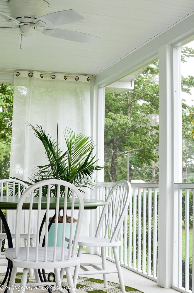 sheer outdoor curtains, palm tree, and a table with chairs