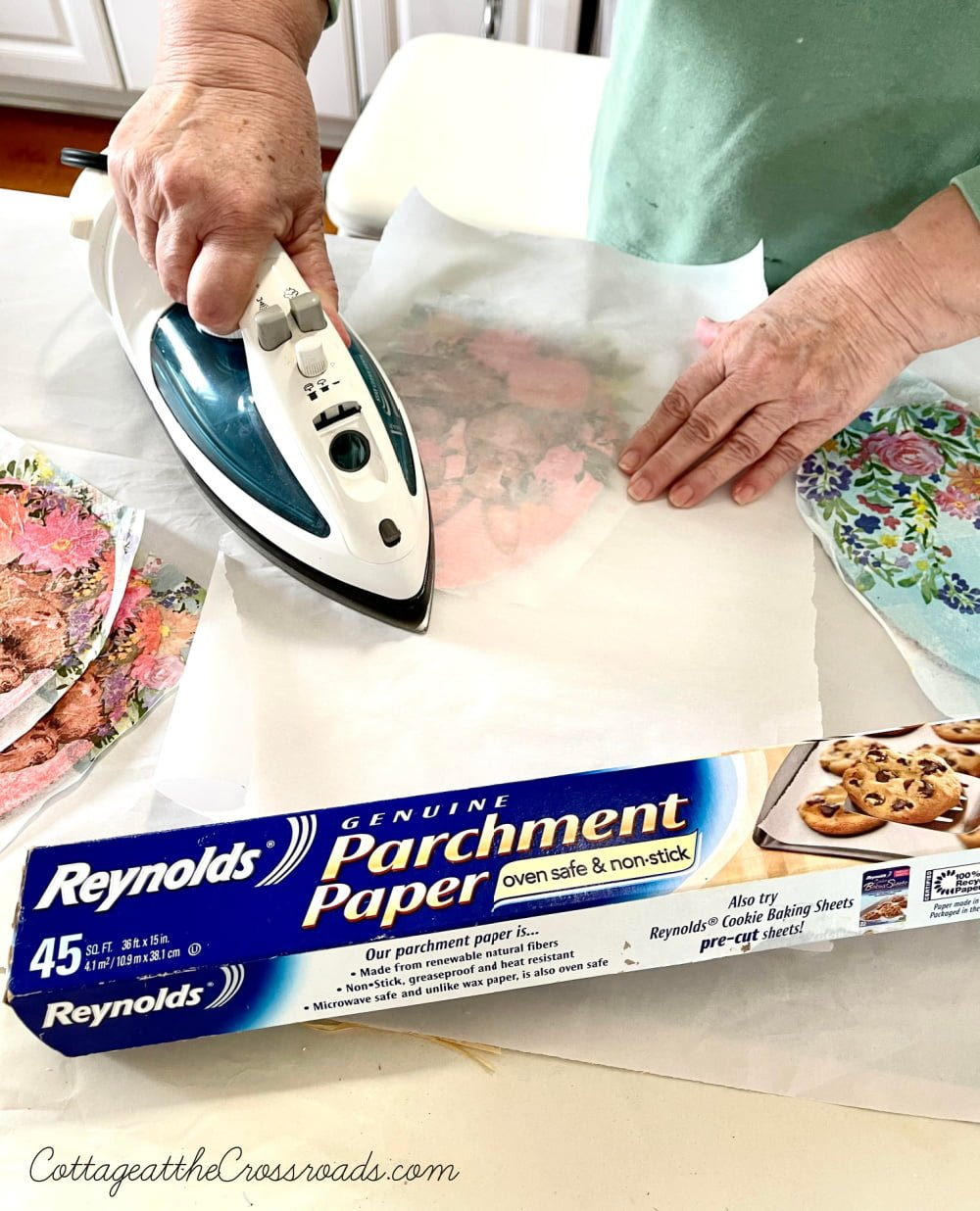 using an iron and parchment paper to remove wrinkles from a decoupaged wooden egg
