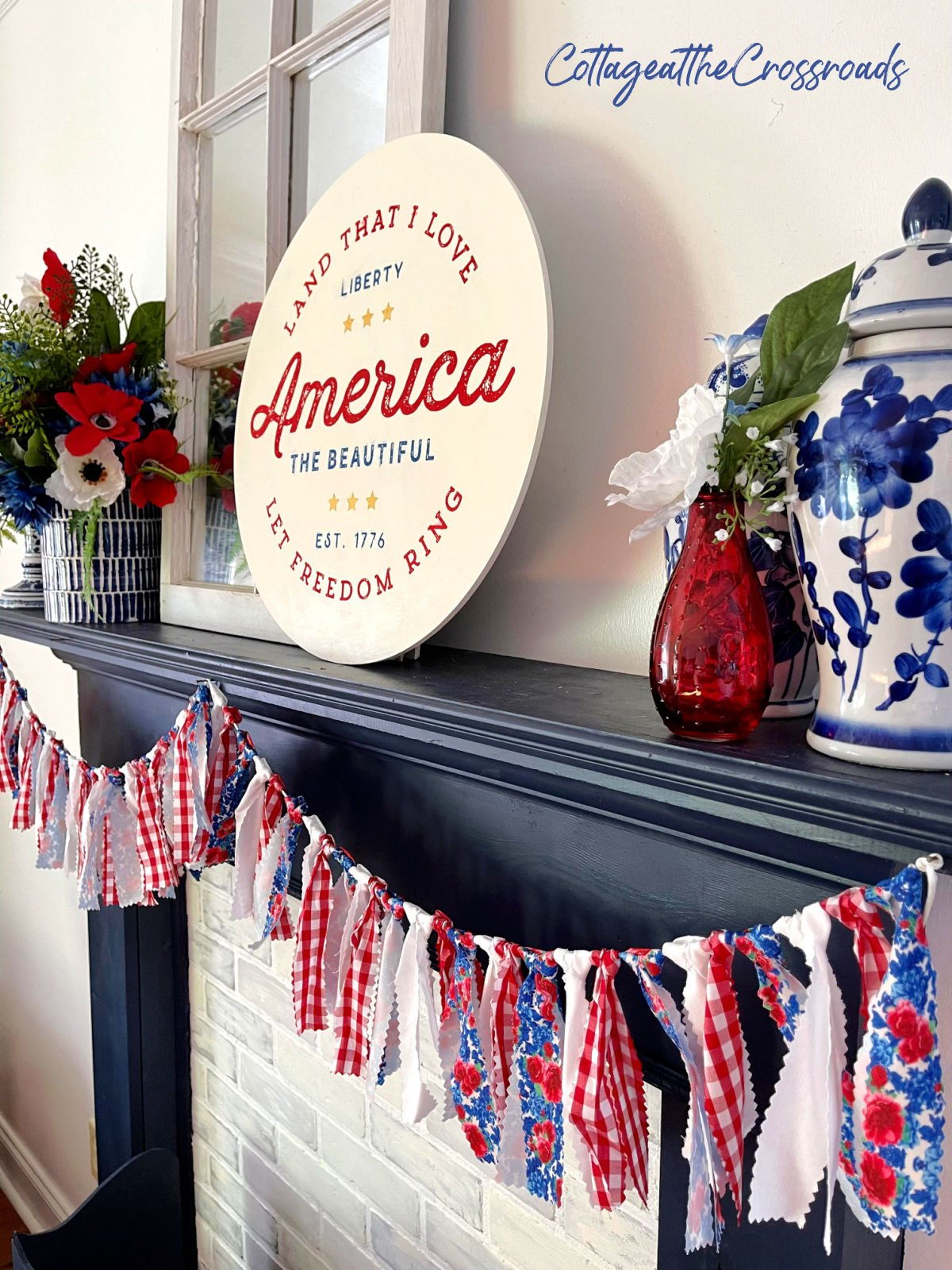 red, white, and blue garland and other patriotic decorations on a navy mantel