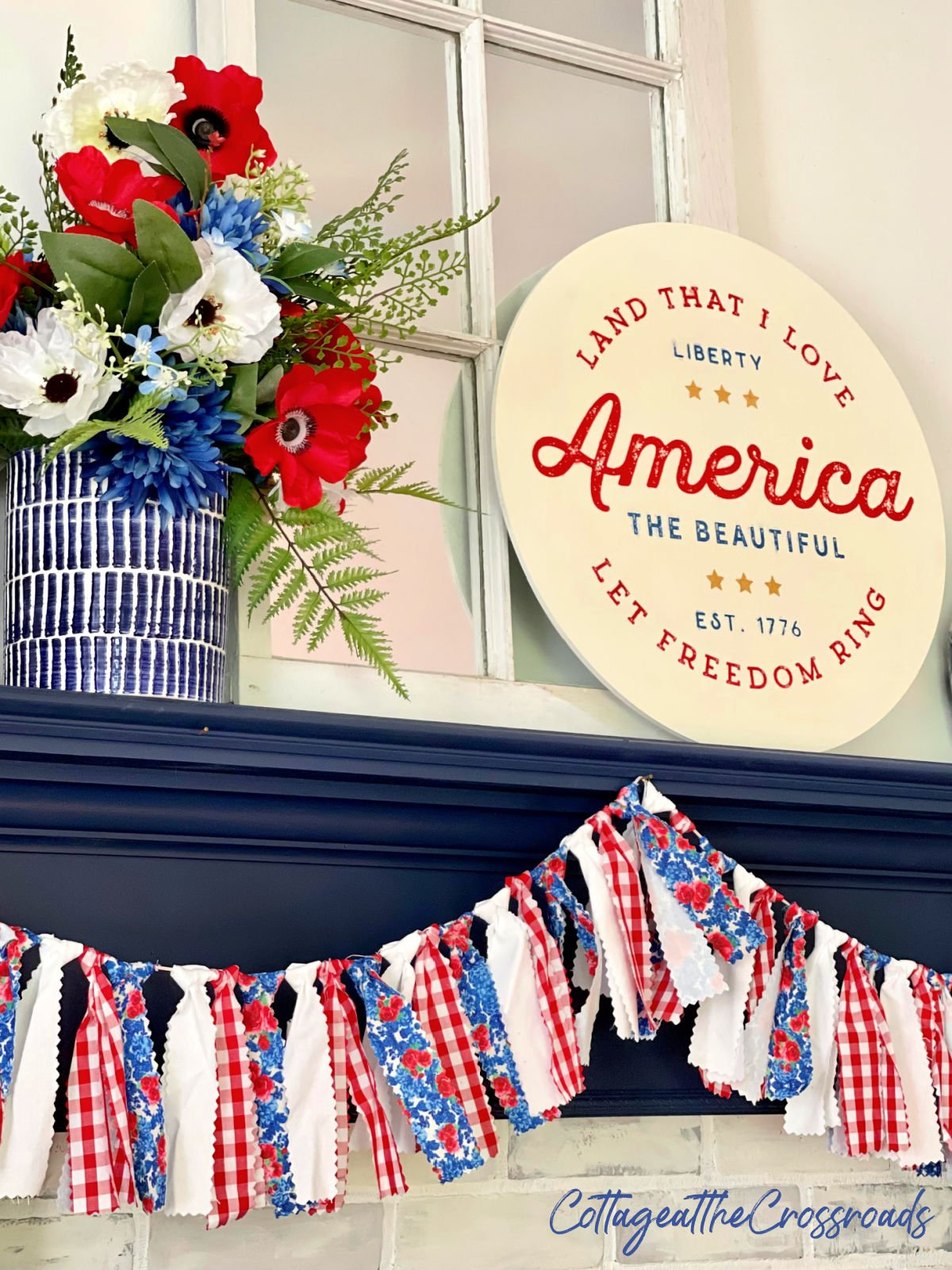 round patriotic sign, floral decorations, and garland on a navy mantel