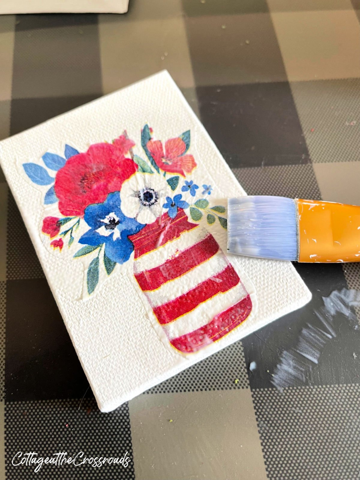applying Mod Podge onto the front of the cut out napkin design