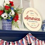 round patriotic sign, floral display, and garland on a navy mantel