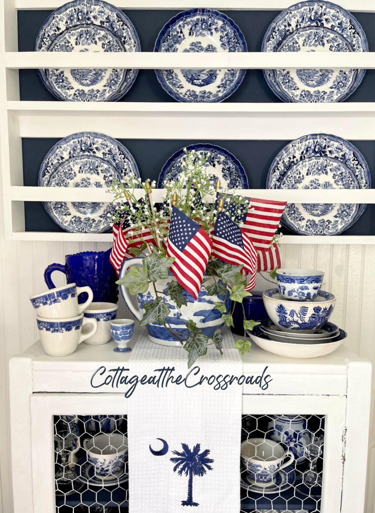 blue and white china displayed in a wooden plate rack with flags tucked down inside a jar