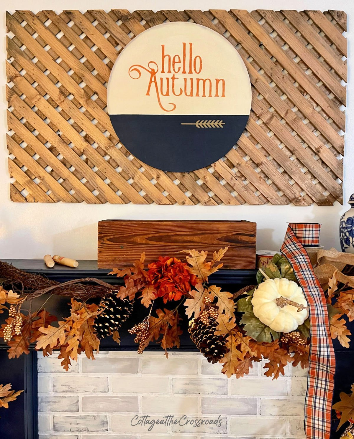 wooden round with the words Hello Autumn mounted on a wood lattice panel