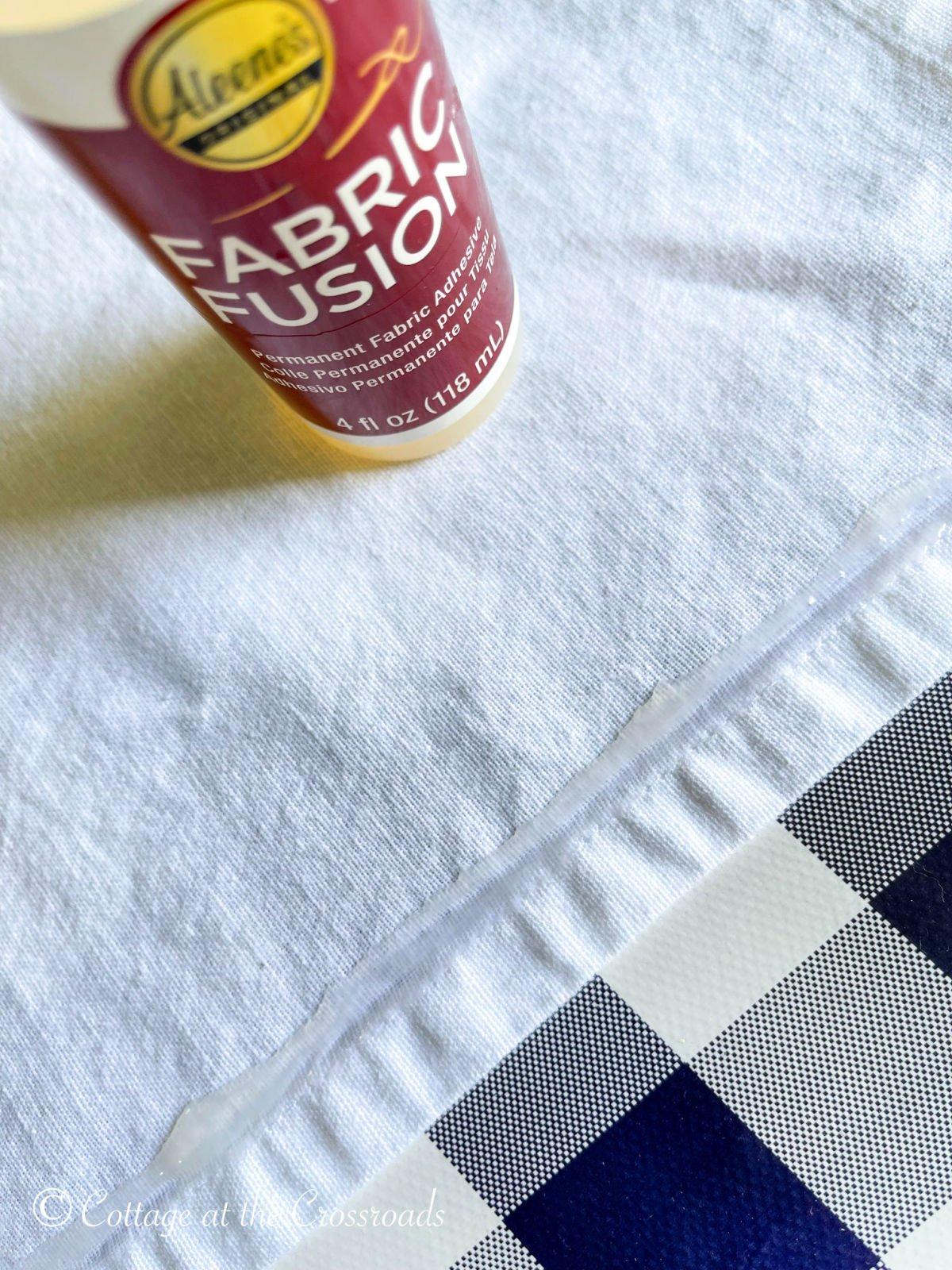 applying fabric glue to tea towel