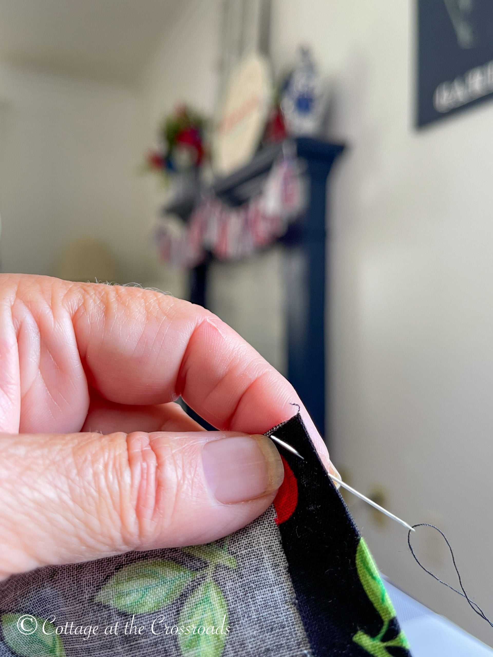 hand holding fabric with needle inserted