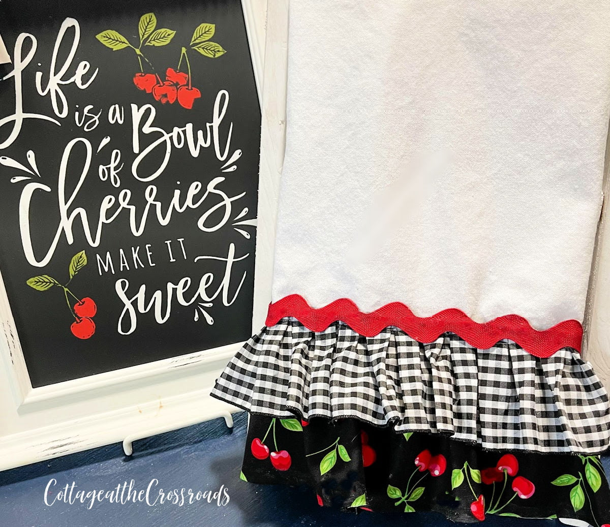 ruffled tea towel beside a sign that says Life is a Bowl of Cherries