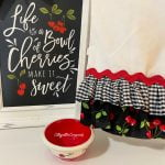 ruffled tea towel beside a sign about cherries and a bowl with cherries on it