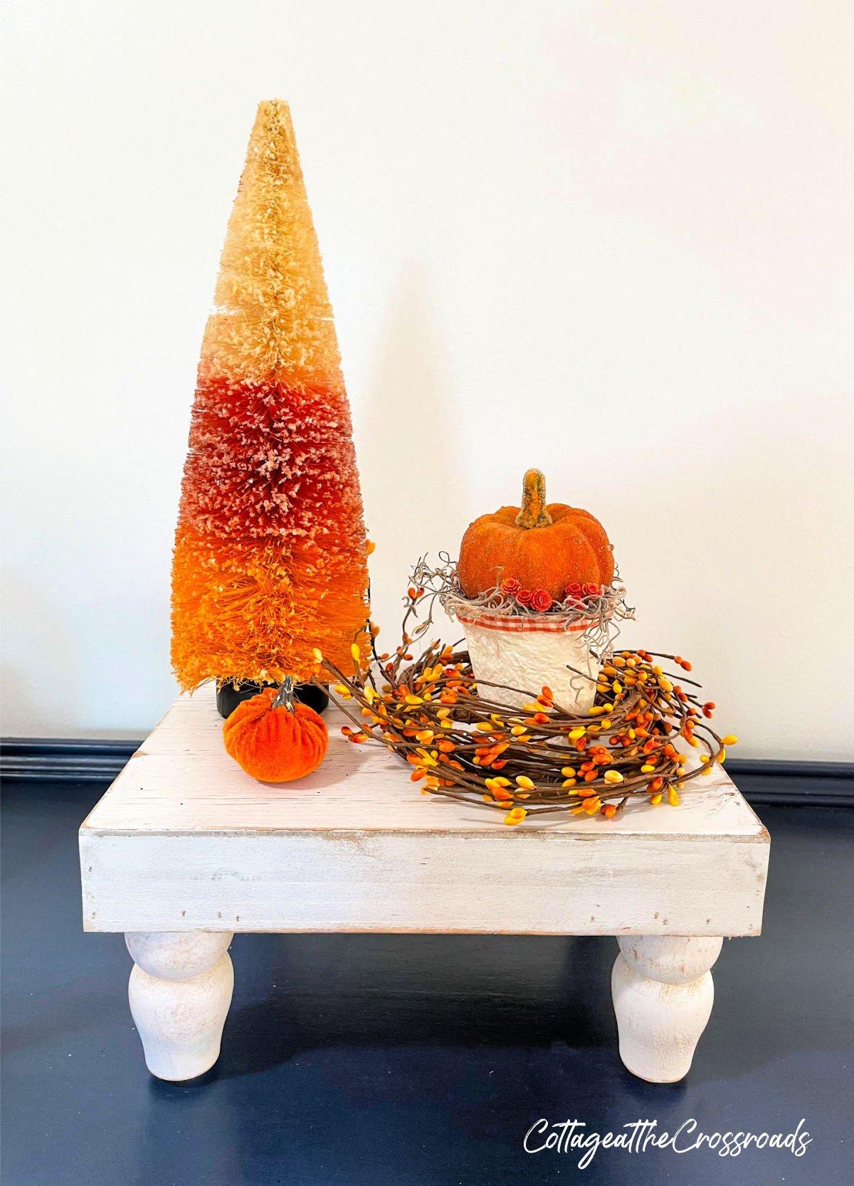 peat pot pumpkin holder and bottle brush tree on a white riser