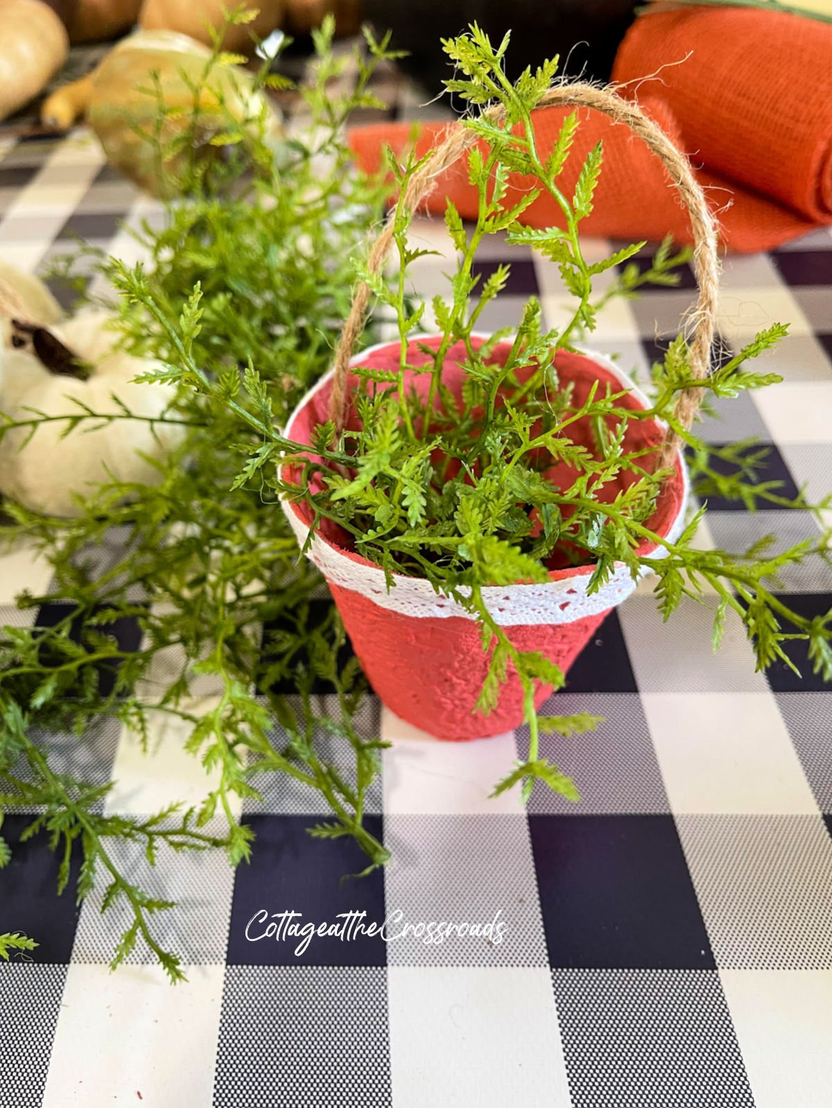 painted peat pot with faux greenery inside